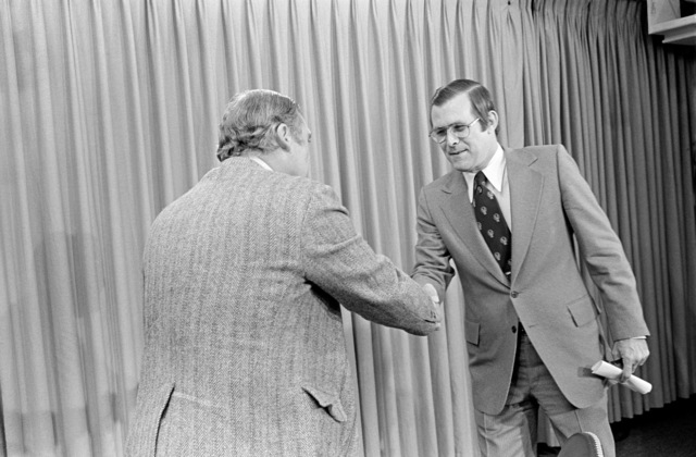 Secretary of Defense Donald Rumsfeld shakes hands with Mr. Jim Clark from WMAL-TV, Baltimore, Md., during an interview at the Pentagon studio in Washington, D.C., on Nov. 4, 1976. OSD Package D-1998-OSD-76-110015 (PHOTO by Ron Hall, CIV) (Released)