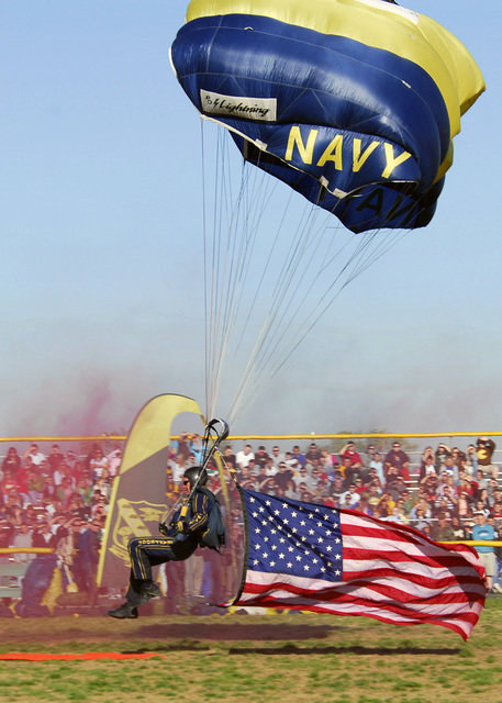 U.S. Navy CHIEF Special Warfare Operator Larry Summerfield,, member of the U.S. Navy Leap Frogs (the U.S. Navy Parachute Demonstration Team), delivers the U.S. National Flag (National ENSIGN) to the football field during a performance at North Bullitt High School in Shepherdsville, Ky., on April 27, 2007. (U.S. Navy photo by Mass Communication SPECIALIST 1ST Class Terry Matlock) (Released)