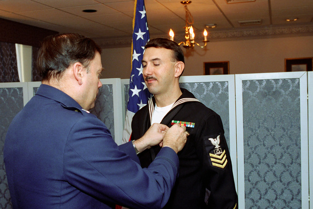 U.S. Air Force MAJ. GEN. John P. Jumper, left, presents a Navy Achievement Medal to U.S. Navy Mess Management SPECIALIST 1ST Class Michael Ryan, from the Office of the Secretary of Defense, during an award ceremony at the Pentagon, Washington, D.C., on Jan. 4, 1993. Package No. A07D- 00083 (DOD PHOTO by Robert D. Ward) (Released)