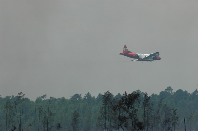Lake City, FL, May 15, 2007 -- A large tanker plane flies low over the forest on its way to a dump of fire retardant.  The tanker is part of the effort to bring the Florida Bugaboo Fire under control.  The U.S. Department of Homeland Security's Federal Emergency Management Agency (FEMA) has authorized 5 Fire Management Assistance Grants between March 27th  and May 10th 2007,  to help Florida fight fires in 16 counties.  Mark Wolfe/FEMA