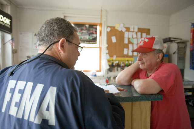 [Severe Storms and Inland and Coastal Flooding] Bound Brook, NJ,  May 16, 2007 -- Community Relations field worker Luis Miranda delivers disaster information to a resident of Bound Brook, N.J. Bound Brook was flooded by the nor'easter storm.  Andrea Booher/FEMA