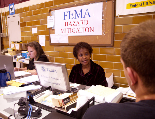 [Severe Storms, Tornadoes, and Flooding] Sioux Falls, SD, June 5, 2007 -- Delores Avington, center, an application service specialist with FEMA Region 6, helps a disaster survivor at the Aberdeen Disaster Recovery Center. State, FEMA, SBA and volunteer agency representatives are offering services and information to help speed recovery from the May4-5, 2007, storms. Amanda Bicknell/FEMA
