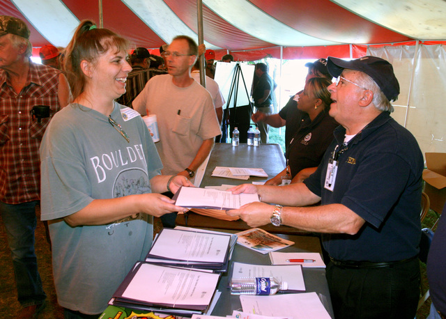 [Severe Storms, Tornadoes, and Flooding] Greensburg, KS,  June 7, 2007  -- Greensburg resident Debra Wilder receives a mitigation information packet from FEMA Disaster Assistance Employee George Freiedrich at a town meeting in Davis Park.  Lions Clubs from across Kansas sponsored the meeting and fed the estimated 800 attendees.  Photo by Greg Henshall / FEMA