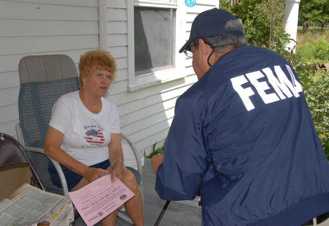 [Severe Storms and Flooding] Agency, MO, 6-23-07 -- FEMA Community Relations Specialist Luis Miranda talks with Dorothy Lavnick who received her FEMA housing check in 5 days, but now needs to fill out her SBA loan application to be considered for other FEMA aid.  Community Relation Specialists are out in the flood damaged area to let people know about registering for FEMA aid that may be available to them under the Individual Assistance Program.  Marvin Nauman/FEMA photo