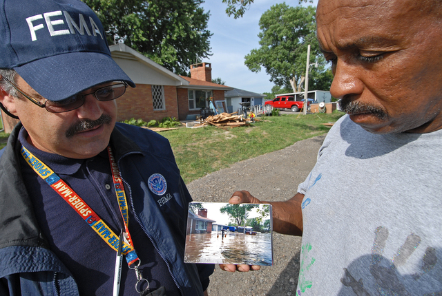 [Severe Storms and Flooding] Agency, MO, 6-23-07 -- Flood victim Robert Johnson shows Community Relations Specialist Luis Miranda a photograph of his home during the flooding.  Mr. Johnson is repairing his flood damaged home with aid he received from FEMA.  Community Relations Specialists are out in the flood damaged area to let people know about registering for FEMA aid that may be available to them under the Individual Assistance Program.  Marvin Nauman/FEMA photo