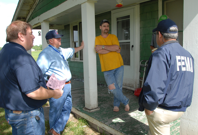 [Severe Storms and Flooding] Agency, MO, 6-23-2007 -- Community Relations Specialists Luis Miranda and Richard Farrington and Buchanam Co EMA Director talk with Flood Victim Renter Ronnie Gregg who may qualify for FEMA Aid.  Community Relations Specialists are in the flood damaged area to let people know about registering for FEMA aid that may be available to them under the Individual Assistance Program.  Marvin Nauman/FEMA photo
