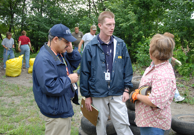 [Severe Storms and Flooding] Rosendale, MO, 6-30-07 -- FEMA Community Relations Specialists Luis Miranda and Chad McCormick talk with Dawn Blair who organized a group of clean up volunteers.  Community Relations Specialists are in the flood damaged area to let people know about Disaster Recovery Centers opening up and registering for FEMA aid that may be available to them under the Individual Assistance Program. Marvin Nauman/FEMA photo