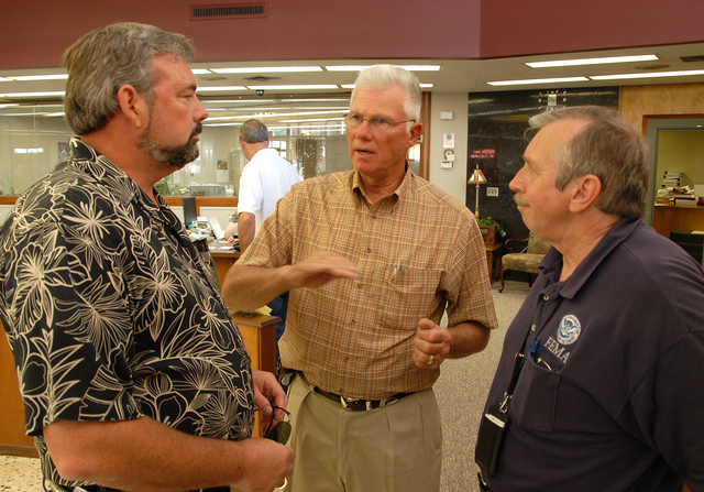 [Severe Storms, Tornadoes, and Flooding] Kingfisher, OK, August 19, 2007 -- Kingfisher vice Mayor Steve Richards and City Manager Richard Reynolds talk with FEMA PIO Charles Henderson at City Hall after a press briefing.  FEMA's Individual Assistance Program has grants and other aid available to help flood victims recover from floods.  Marvin Nauman/FEMA photo