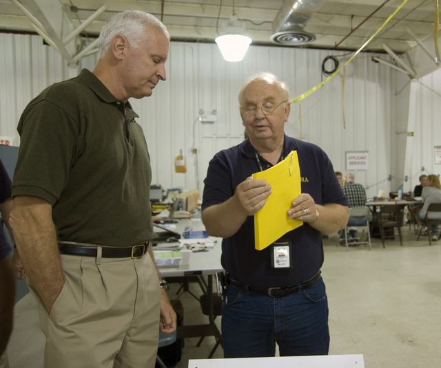 [Severe Storms and Flooding] Rushford, MN, August 30, 2007 -- Sam Kniston, FEMA DRC manager shows Edward G. Buikema, FEMA Region V Regional Administrator, a report listing the number of applicants who have come to the DRC in Rushford.  FEMA is working with individuals, state and local representatives to help them recover from the floods.  Patsy Lynch/FEMA