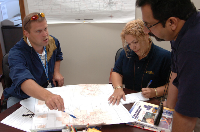 [Severe Storms, Flooding, and Tornadoes] Bucyrus, Ohio, August 30, 2007 -- Crawford County, Ohio Emergency Manager Tim Flock briefing FEMA Community Relations (CR) team members Marilyn Cortes and Choudhry Hussain. FEMA community relations staff assist local emergency managers in the rapid and accurate delivery of both local and FEMA disaster related information. Mike Moore/FEMA