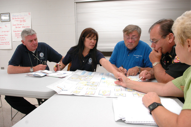 [Severe Storms, Flooding, and Tornadoes] Findlay, Ohio, August 30, 2007 -- FEMA Community Relations (CR) representatives Doug Parker (far left) and Cindy Yee-Choy (center left) ask local officials about the areas hit hardest by the recent Ohio floods. CR representatives go door to door to disseminate information about FEMA programs directly to the people affected by a disaster. Mark Wolfe/FEMA