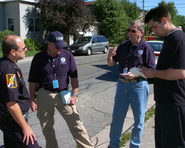 [Severe Storms, Flooding, and Tornadoes] Bluffton, Ohio September 1, 2007 -- An ad hoc street meeting between (left to right) Bluffton Police Chief Rick Skilliter, FEMA Community Relations (CR) lead Dan Curry, FEMA Public Information Officer (PIO) Tim Tyson, and Lima News reporter Brian Evans. Sharing disaster recovery information is critical to helping a community quickly and efficiently return life back to normal; North Central Ohio is in the recovery phase from the summer floods. Mike Moore/FEMA