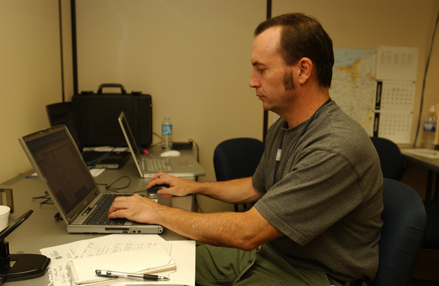 [Severe Storms, Flooding, and Tornadoes] Findlay, Ohio  September 4, 2007 --   FEMA photographer Mark Wolfe working on a computer testing transmission lines at the Joint Field Office (JFO).  During a disaster FEMA brings in photographers to document response and recovery efforts.  John Ficara/FEMA