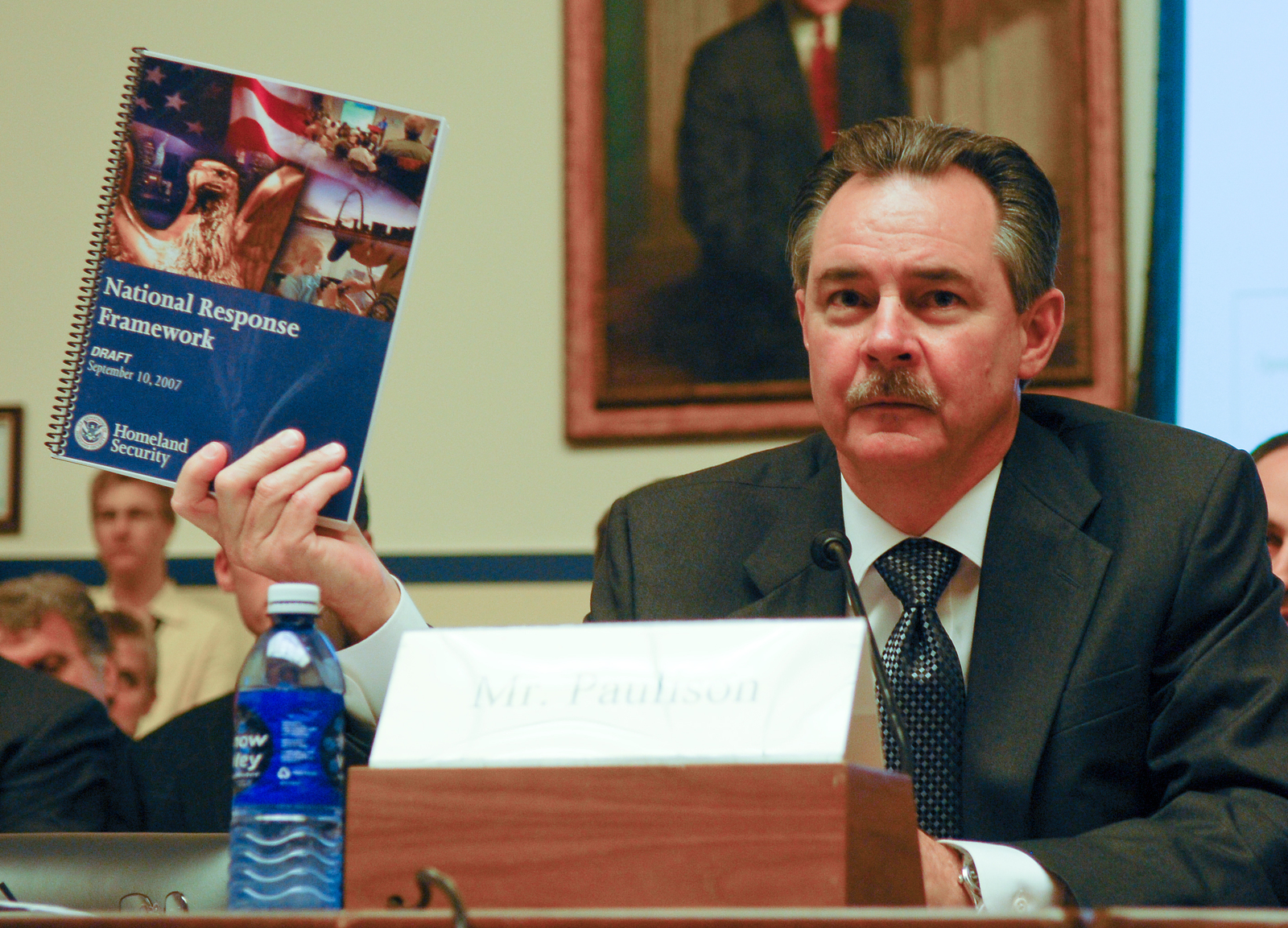 """Washington, DC, September 11, 2007 -- FEMA Administrator R. David Paulison holds up a copy of the National Response Framework at The House Transportation and Infrastructure, Subcommittee on Economic Development, Public Buildings and Emergency Management hearing on """"Readiness in the Post Katrina and Post 9/11 World:  An Evaluation of the New National Response Framework"""".  FEMA/Bill Koplitz"""