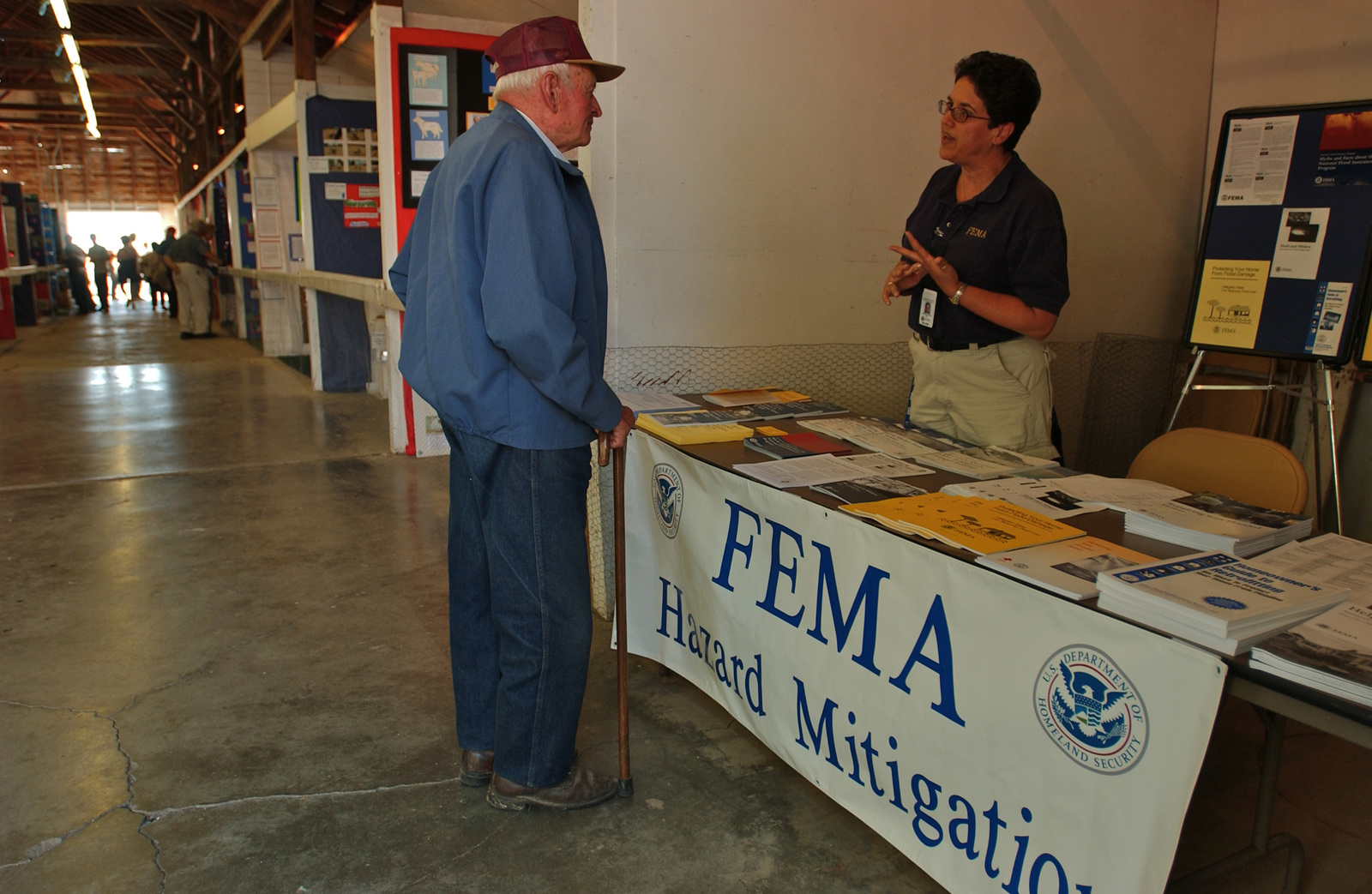 [Severe Storms, Flooding, and Tornadoes] Upper Sandusky, Ohio, September 13, 2007 -- FEMA representative Yvonne Whitely talks with a local homeowner at the Wyondot County Fair about damages to his home due to recent flooding. FEMA mitigation representatives  reach out to the community to provide information on repair and prevention techniques. John Ficara/FEMA
