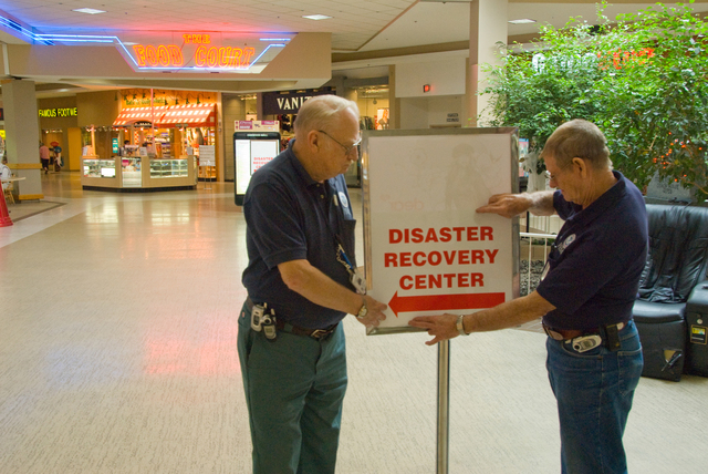 [Severe Storms, Tornadoes, and Flooding] Enid, OK, September 19, 2007 -- FEMA Disaster Recovery Center (DRC) Specialists Alton Jones and Paul Lovell put a Sign up in the Enid Mall pointing the way to the Disaster Recovery Center that is set up there.  DRC's provide applicants with information about FEMA aid and help filling out their application.  Marvin Nauman/FEMA photo