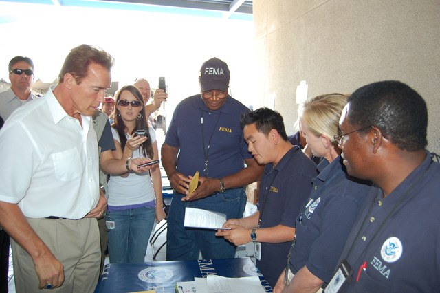 [Wildfires] El Cajon, CA, October 28, 2007 -- Nick Ho, a Community Relations Specialist from Austin, hands a FEMA assistance information pamphlet to California Governor Arnold Schwarzenegger during his visit Sunday at the Local Assistance Center (LAC) at Cuyamaca College in El Cajon.  Other CR Team members looked on as Ho explained FEMA's recovery efforts at the center.  FEMA is just one of more than 25 local, county, state, and federal agencies represented at the LAC designed to assist victims of the recent wildfires.  FEMA Photo by Gene Romano.