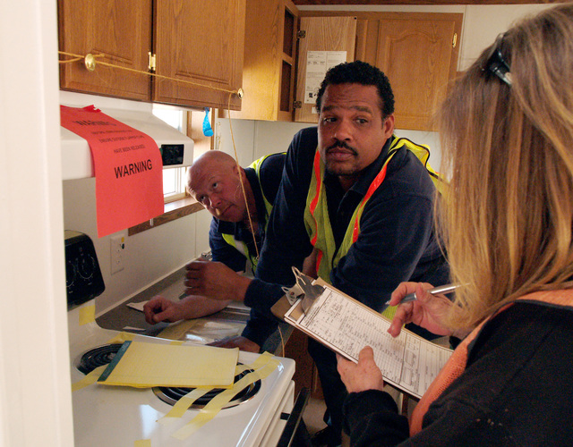 [Wildfires] March Air Force Base, CA, November 20, 2007 -- Anthony Johnson, a FEMA Individual Assistance liaison, center, and Deborah Maggard, FEMA deputy site manager for mobile home inspections, review mobile home inspection inside the kitchen of the first mobile home slated for use in the wake of the wild fires in Southern California, while Edward Coulter, a FEMA worker examines the stove?s fan. Amanda Bicknell/FEMA