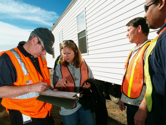 [Wildfires] March Air Force Base, CA, November 20, 2007 -- Don Chapman, left, a contractor with CH2M Hill, Inc., Deborah Maggard, FEMA deputy site manager for mobile home inspections, Don Keller, of Babcock Services (FEMA sub-contractor to CH2M Hill, Inc.), and Anthony Johnson, a FEMA Individual Assistance liaison, discuss the inspection of the first mobile home slated for use in the aftermath of the devastating wild fires. The kitchen cabinets were tied shut for transport to the base. Amanda Bicknell/FEMA