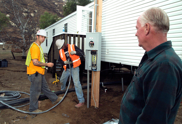 [Wildfires] Delzura, CA, December 5, 2007 -- FEMA applicant Jon Grice, right, watches as electricians Adam Murschel, left, and Franklin wood, both of O'Donnell Electric, install the wiring for the mobile home Grice and his wife will live in temporarily while they begin rebuilding. The couple lost their home during the wildfires in October. Amanda Bicknell/FEMA