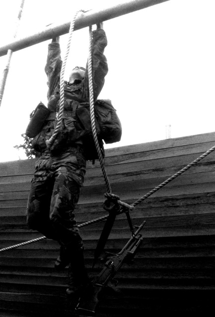 A member of the British Army 3rd Battalion, Royal Anglian Regiment, prepares to rappel from a horizontal bar during a cities assault training course