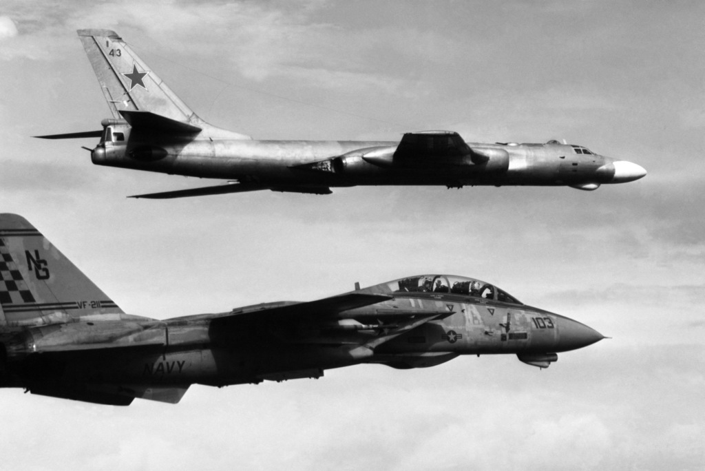 A right side view of a Soviet Tu-16 Badger-C aircraft, background, being escorted by an F-14A Tomcat aircraft from Fighter Squadron 211 (VF-211), based aboard the nuclear-powered aircraft carrier USS Nimitz (CVN-68). OFFICIAL U.S. NAVY PHOTO (RELEASED)