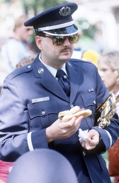 AIRMAN First Class (AMN) Gregory D. Grooms grabs a quick lunch after participating in a parade. Grooms is a member of the 528th Air Force Band of Mid-America which is performing in several Illinois cities