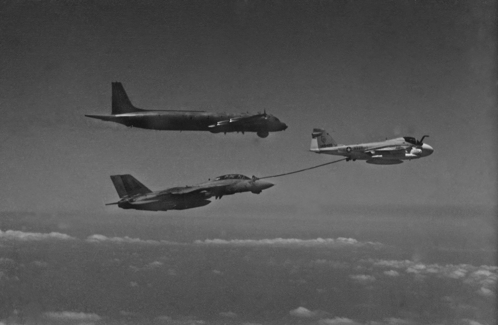 An air-to-air air right side view of a KA-6D Intruder aircraft refueling an F-14A Tomcat aircraft. A Soviet Il-38 May aircraft is in the background. OFFICIAL U.S. NAVY PHOTO (RELEASED)