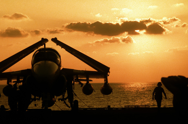 JO1 Patrick E. Winter ....An A-6E Intruder aircraft parked on the flight deck of the nuclear-powered aircraft carrier USS Nimitz (CVN-68) is silhouetted against the setting sun. OFFICIAL U.S. NAVY PHOTO (RELEASED)