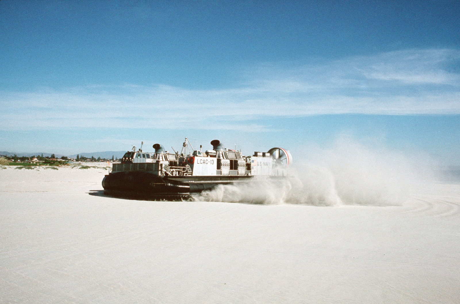 JOCS Theresa L. Dunn/PH1 Paul Pappas Naval Air Station, North Island, Calif....Trailed by a cloud of blown sand, the air cushion landing craft LCAC-13 moves up Breakers Beach during an amphibious warfare demonstration. OFFICIAL U.S. NAVY PHOTO (RELEASED)