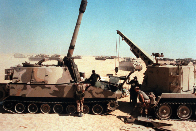 Mechanics work in the engine compartment of an M-109A1 155mm self-propelled howitzer, left, during the joint U.S./Egyptian exercise Bright Star '85. The M-578 light armored recovery vehicle at right was used to remove the howitzer's engine