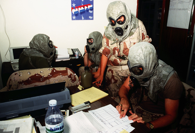 Members of the 24th Infantry Division and 101st Airborne Division tend to paperwork while wearing nuclear-biological-chemical warfare gear for a drill during Operation Desert Shield