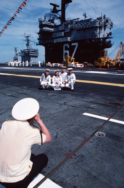 PH1 (AC) Scott M. Allen Naval Base, Norfolk, Va....A Soviet officer photographs a group of his comrades in front of the island on the aircraft carrier USS John F. Kennedy (CV-67). The Slava class guided missile cruiser Marshal Ustinov (CG-088), the Sovremenny class guided missile destroyer Otlichnyy (DDG-434) and the oiler Genrikh Gasanov are making the first-ever Soviet naval visit to a U.S. military port. OFFICIAL U.S. NAVY PHOTO (RELEASED)