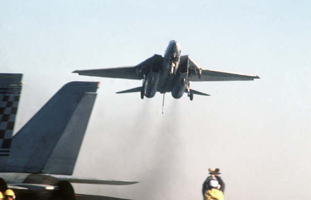 PH1 Anthony J. Kmiecik Pacific Ocean....An F-14A Tomcat aircraft flies by the USS Independence (CV-62) with tailhook and landing gear down during carrier qualifications of Reserve Carrier Air Wing 30 (CVWR-30) off the coast of southern California. OFFICIAL U.S. NAVY PHOTO (RELEASED)