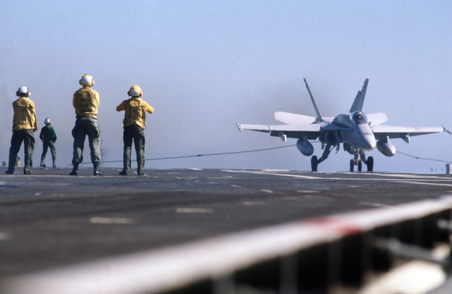PH1 Anthony J. Kmiecik Pacific Ocean....Crewmen signal and the cable arrests an F/A-18 Hornet aircraft landing on the USS Independence (CV-62) during carrier qualifications of Reserve Carrier Air Wing 30 (CVWR-30) off the coast of southern California. OFFICIAL U.S. NAVY PHOTO (RELEASED)
