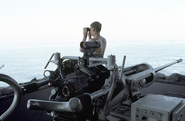 PH1 DeWayne Smith Persian Gulf....A barge worker scans the horizon while manning a Mark 68 20mm gun aboard the barge Wimbrown 7. OFFICIAL U.S. NAVY PHOTO (RELEASED)