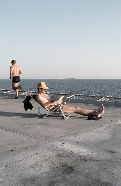 PH1 DeWayne Smith Persian Gulf....A sailor relaxes in the sun on the helicopter pad of the barge Wimbrown 7. OFFICIAL U.S. NAVY PHOTO (RELEASED)