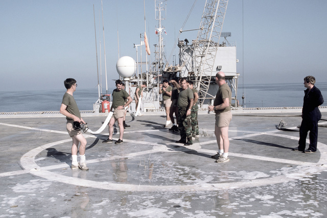 PH1 DeWayne Smith Persian Gulf....Barge workers receive instructions on hosing down the helicopter pad aboard the barge Wimbrown 7. OFFICIAL U.S. NAVY PHOTO (RELEASED)