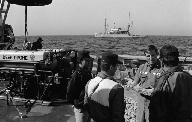 PH1 Felimon Barbante Sea of Japan....Civilian contract personnel discuss the launching of the unmanned submersible Deep Drone from the deck of the fleet tug USNS Narragansett (T-ATF-167) as the salvage ship USS Conserver (ARS-39) passes by during salvage operations for downed Korean Air Lines Flight 007 (KAL-007). The commercial jet was shot down by Soviet aircraft over Sakhalin Island on Aug. 30, 1983. All 269 passengers and crewmen were killed. OFFICIAL U.S. NAVY PHOTO (RELEASED)