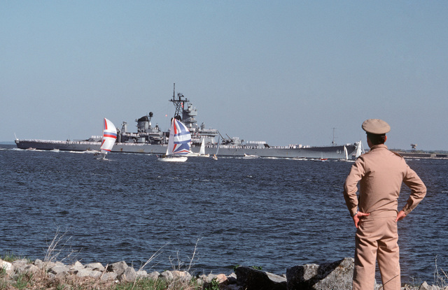 PH2 Milton Savage, USNR Fort Monroe, Va....A Navy officer watches from shore as the battleship USS Iowa (BB-61), its crew manning the rails, passes by the fort near Norfolk, Va. The Iowa is returning home to Norfolk after an explosion in the No. 2 16-inch gun turret killed 47 sailors during routine gunnery exercises 330 miles northeast of Puerto Rico on April 19. OFFICIAL U.S. NAVY PHOTO (RELEASED)
