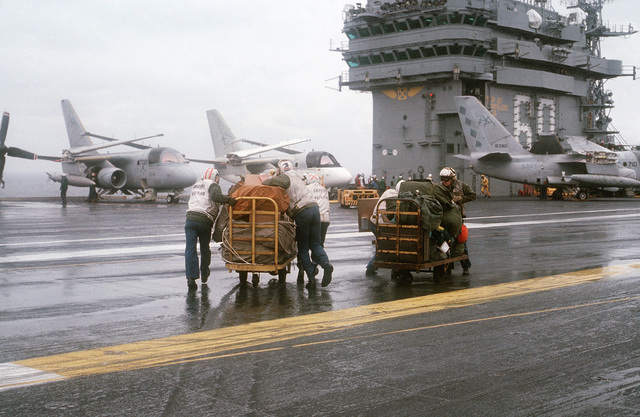PH2 Tracy Lee Didas Atlantic Ocean....Three crewmen, left, push a cart full of mail bags just unloaded from an CH-53 Sea Stallion helicopter across the rain-swept deck of the nuclear-powered aircraft carrier USS Dwight D. Eisenhower (CVN-69). The crewmen on the right are moving toward the helicopter with seabags and luggage belonging to personnel who will return with the helicopter to shore. The Eisenhower is conducting carrier qualifications off the Virginia Capes. OFFICIAL U.S. NAVY PHOTO (RELEASED)