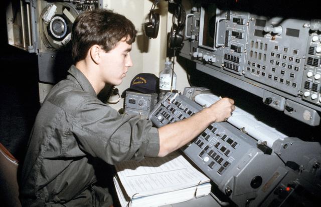 PH2(AC) Scott M. Allen ....An aviation anti-submarine warfare technician performs a preflight check on anti-submarine warfare support equipment aboard an aircraft. OFFICIAL U.S. NAVY PHOTO (RELEASED)