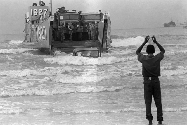 PHCS Ron Bayles Thailand....A beachmaster signals to the operator of utility landing craft 1627 (LCU-1627) as vehicles come ashore during exercise Cobra Gold '86. OFFICIAL U.S. NAVY PHOTO (RELEASED)