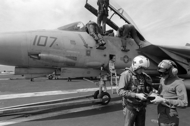 PHCS Ronald W. Bayles South China Sea....Vice Adm. Paul D. Miller, commander, 7th Fleet, checks over his gear with an air crew survival equipmentman before climbing into the cockpit of an F-14A Tomcat aircraft aboard the aircraft carrier USS Kitty Hawk (CV-63). OFFICIAL U.S. NAVY PHOTO (RELEASED)
