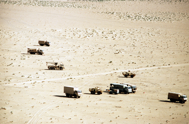 Steyr vehicles and light armored equipment are parked at an outpost during Operation Desert Shield