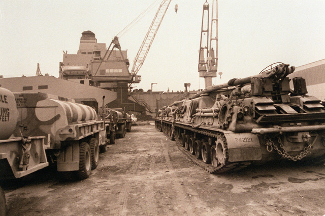 Three M-49 tanker trucks, left, and three M-88 armored recovery vehicles sit on a dock prior to being loaded aboard a cargo ship. The vehicles are assigned to the 24th Infantry Division (Mechanized)