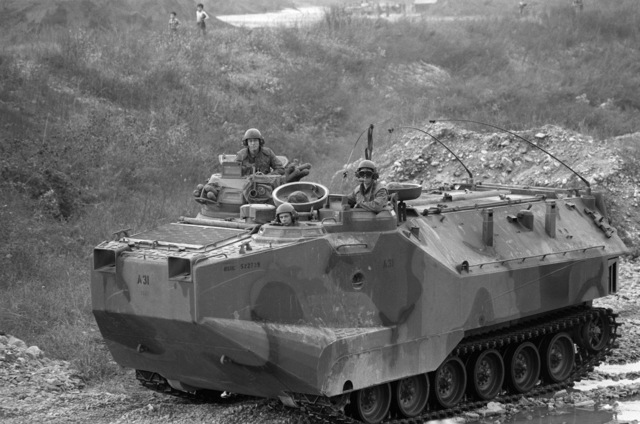 Uncheon Base Camp, South Korea....Marines drive an LVTP-7A1 armored amphibious assault vehicle past two South Korean children during exercise Bear Hunt '87. OFFICIAL U.S. MARINE CORPS PHOTO (RELEASED)