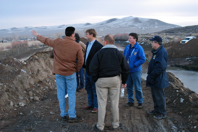 [Severe Winter Storms and Flooding] Fernley, NV, January 10, 2008 -- FEMA FCO Michael Karl (right) listens along with Lyon County Emergency Manager Jeff Page (back to camera), and Small Business Administration (SBA) Team Leader Michael Tippet, as Mayor Todd Cutler describes the canal break to Congressman Dean Heller. The broken canal flooded approximately 200 homes impacting about 2,000 residents.  George Armstrong/FEMA