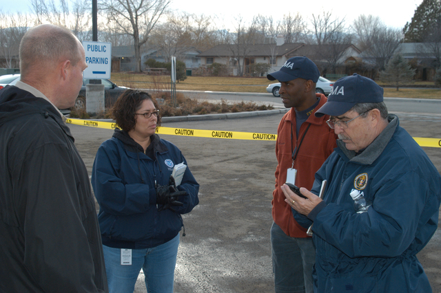 [Severe Winter Storms and Flooding] Fernley, NV, January 10, 2008 -- FEMA Federal Coordinating Officer (FCO) Michael Karl, and Deputy FCO Ken Tingman confer with DRC Manager Gabriella Garibaldi about opening the FEMA Mobile DRC at the Fernley City Hall this afternoon. FEMA and partners will be providing initial services at this location to many of the approximately 2,000 residents impacted by flood and severe storm. George Armstrong/FEMA