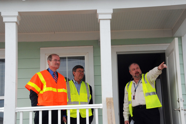 [Hurricane Katrina] Gulfport, MS, January 18, 2008 -- Deputy Administrator and Chief Operating Officer Vice Admiral Harvey Johnson and Acting Associate Deputy Administrator for FEMA's Gulf Coast Recovery Office Jim Stark on the porch of a Mississippi Cottage with MEMA deputy project manager Keith Campbell, at the staging area for the Mississippi Alternative Housing Program. Johnson and Stark toured several sites on the Gulf Coast as part of a visit to assess the recovery progress.  FEMA/Jennifer Smits